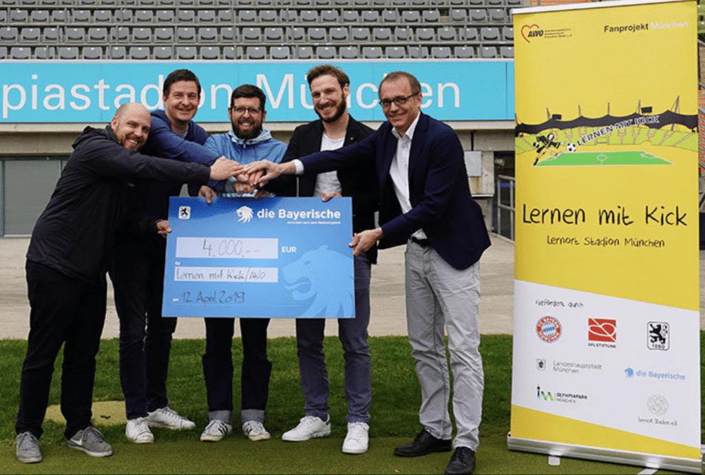 5 Männer halten einen Scheck über 4000€ von Die Bayerische in die Kamera, daneben steht ein Roll Up Banner von Lernen mit Kick
