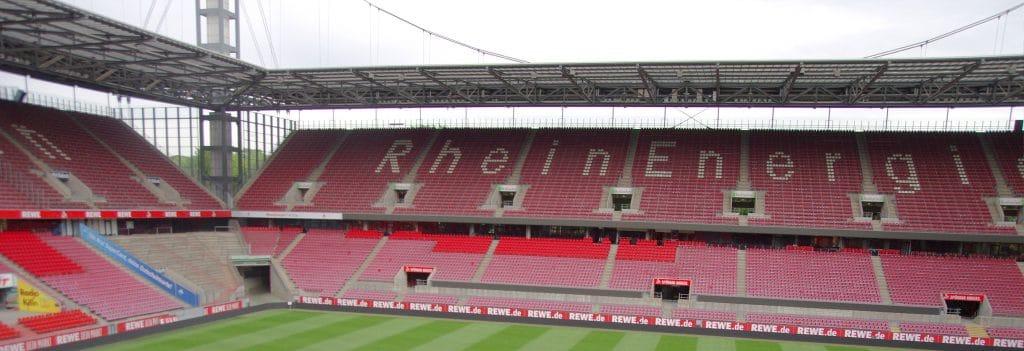 Blick auf die Tribüne eines Stadions mit roten Sitzen und dem Schriftzug Rhein Energie