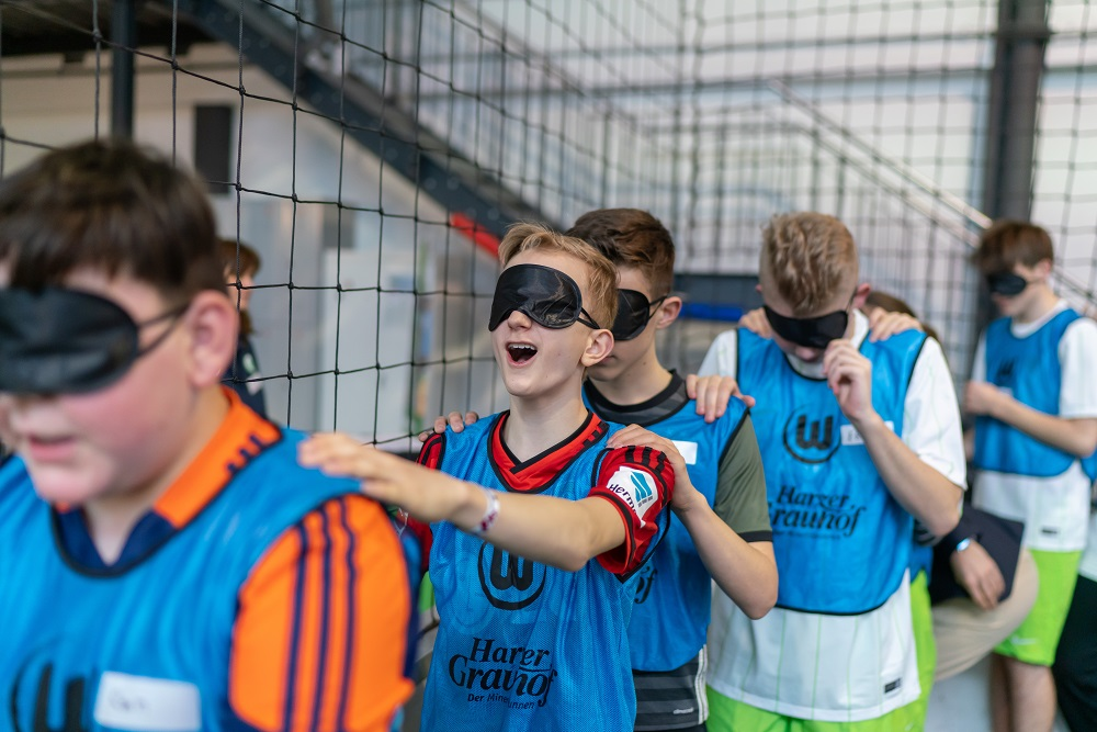 Mehrere Jungen haben blaue Trikots an und laufen hintereinander lang, sie halten sich an den Schultern und tragen Schlafmasken