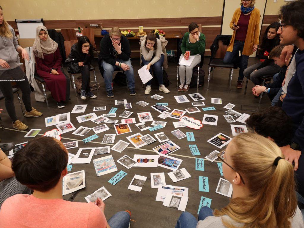 In einem Stuhlkreis sitzen mehrere Menschen, in ihrer Mitte liegen viele beschriebene Zettel und Fotos