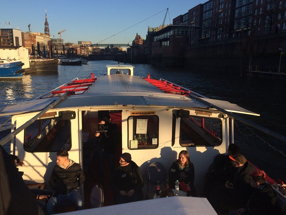 Jugendlich sitzen in einem Schiff das über das Wasser fährt, recht und links sind Häuser
