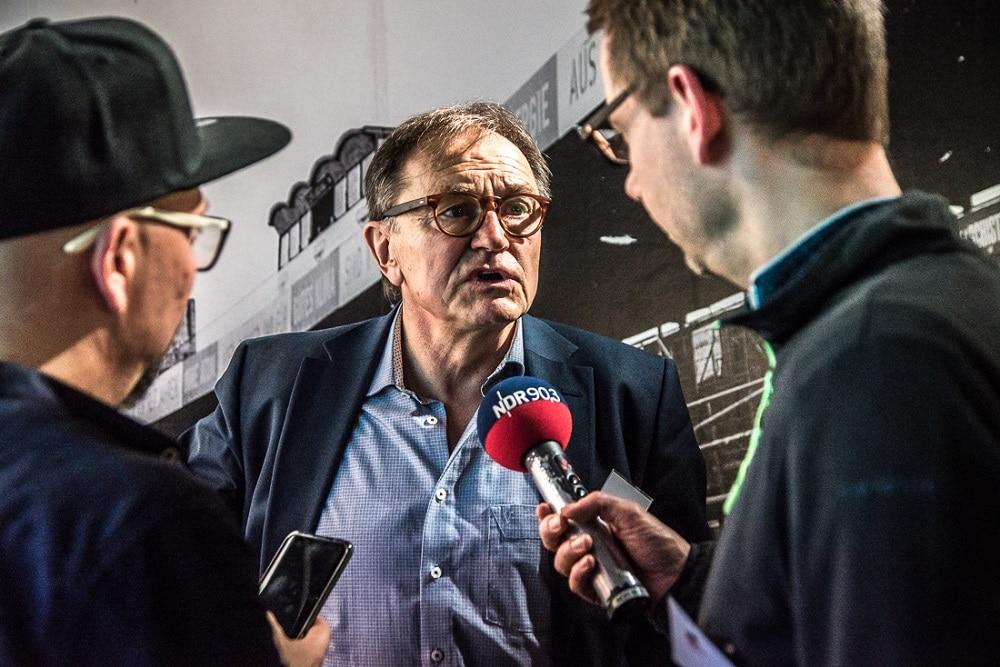 Zwei Männer interviewen einen Mann, dieser spricht in ein Mikrofon auf dem steht: NDR 90,3