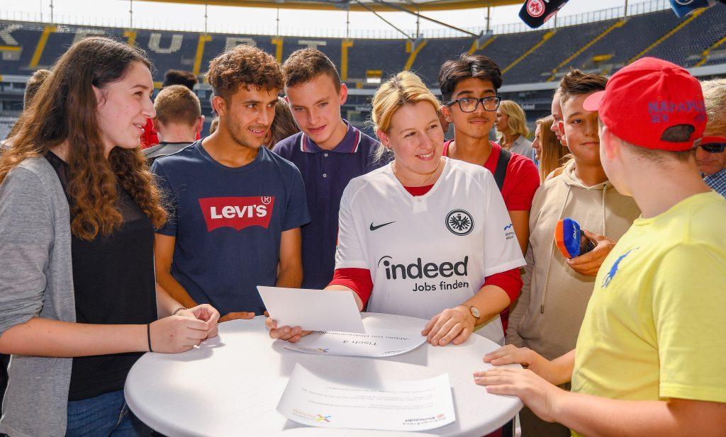 Bundesministerin Franziska Giffey hat ein Trikot an und steht mit mehreren Jugendlichen um einen Tisch herum, sie hält ein Papier in der Hand.