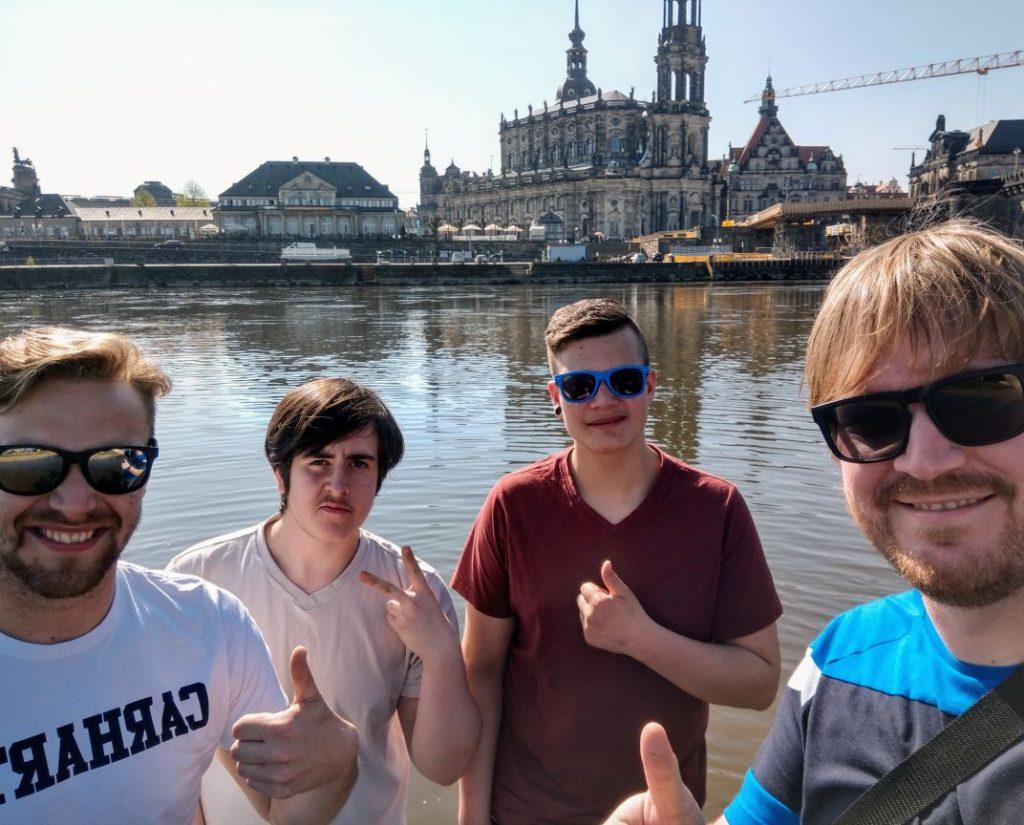 Vier Männer schauen in die Kamera und halten verschiedene Finger in die Kamera, im Hintergrund sieht man Wasser, Häuser, eine große Kirche und einen Kran.