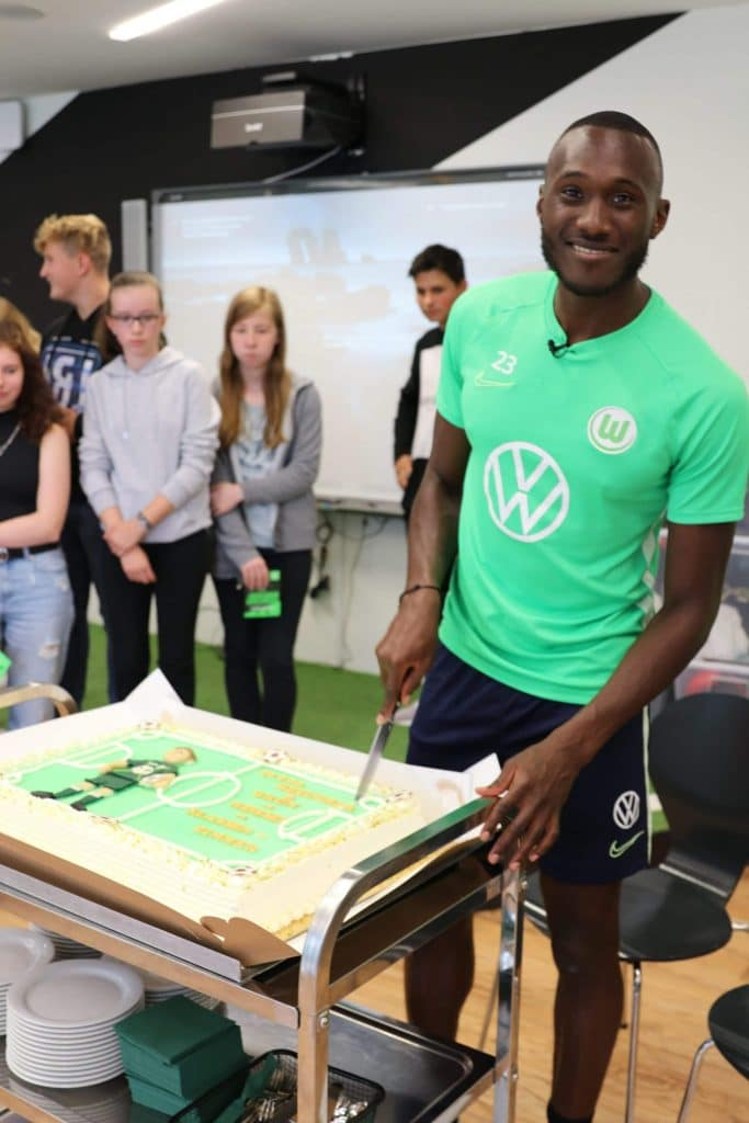 Im Vordergrund schneidet ein Mann mit einem VFL Wolfsburg Trikot einen Kuchen in Stadion Form, im Hintergrund stehen Jugendliche.