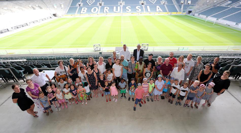 Großes Gruppenfoto von Kindern und Erwachsenen im Stadion von Borussia Mönchengladbach