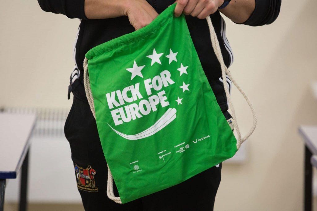 Eine Person hält einen grünen Beutel mit dem Aufdruck Kick for Europe