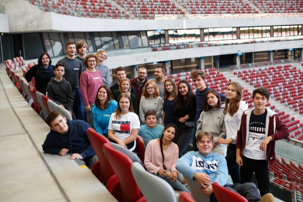 Gruppenfoto von Jugendlichen und Erwachsenen in einem Stadion