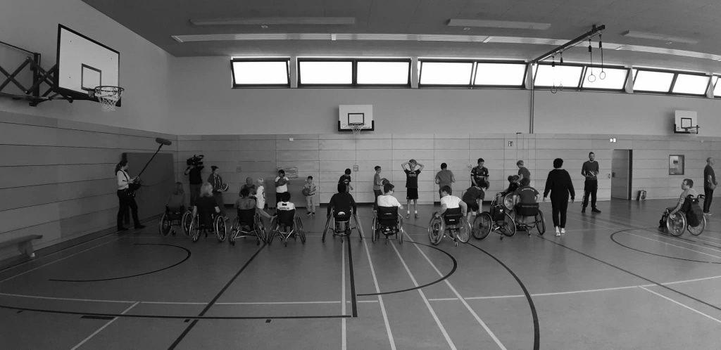 Jugendliche mit und ohne Rollstühle spielen in einer Sporthalle Basketball.
