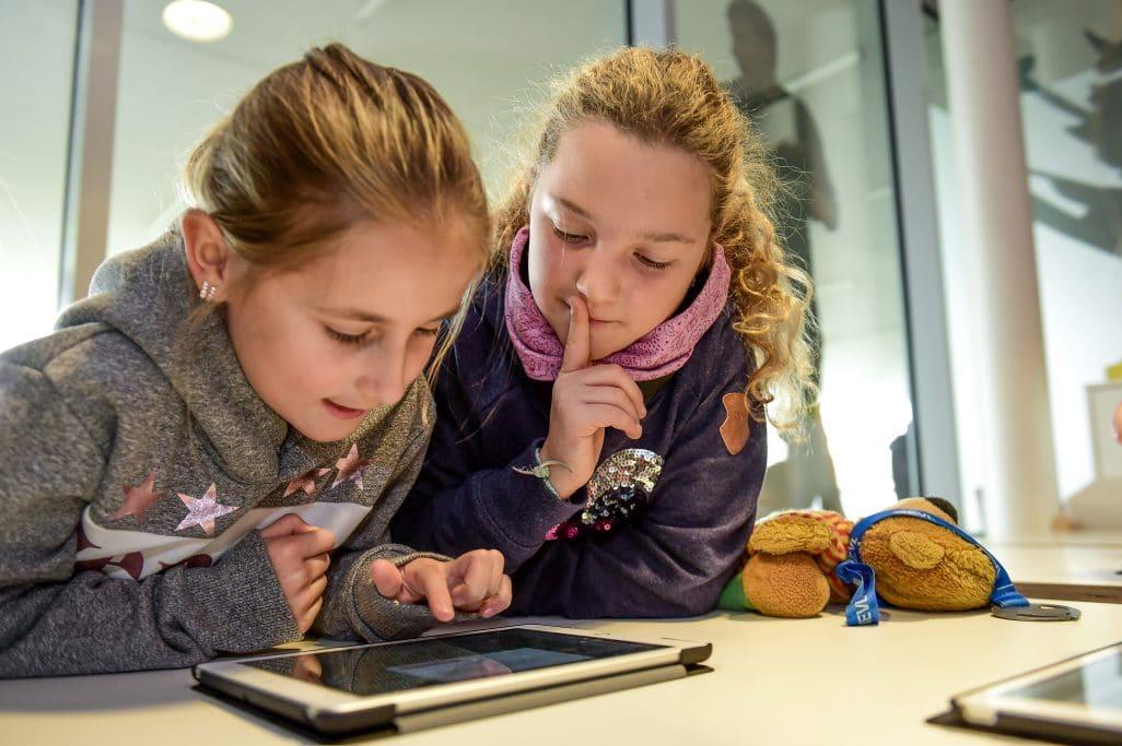 Zwei Kinder schauen in ein Ipad.