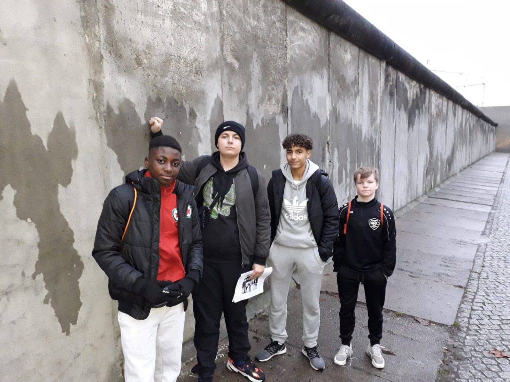 Vier Jugendliche stehen vor einer Mauer und schauen in die Kamera.