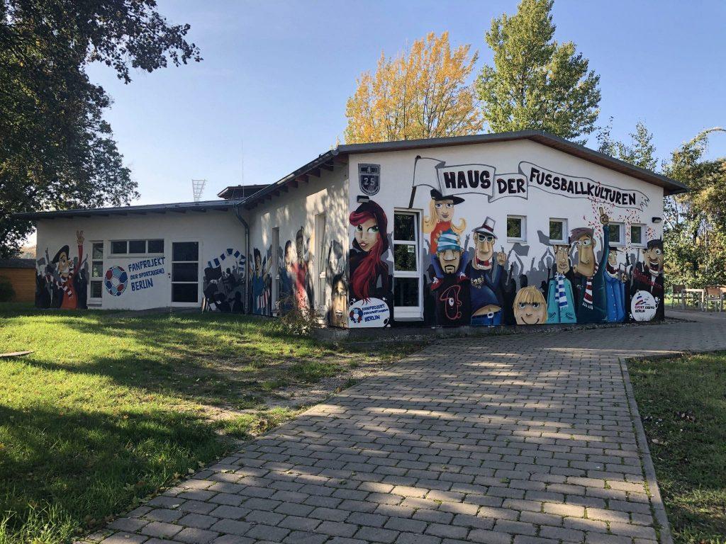 Blick auf das Haus der Fussballkulturen, dieses hat viele verschiedene gemalte Menschen auf der Fassade.